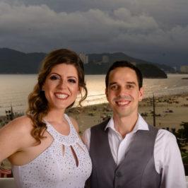 casal de noivos posam em uma sacada com a ilha Urubuqueçaba ao fundo num por do sol em Santos.