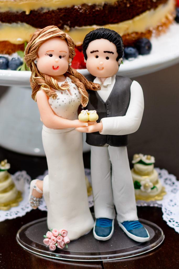 bonequinho dos noivinhos em doce, além de serem réplicas dos noivos reais, seguram nas mãos sapatinhos de neném.