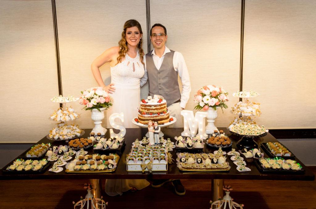 Casal de noivos posam atrás de uma bela mesa de doces e bolo onde um casal de bonequinhos feito de doces é um réplica dos noivos reais.