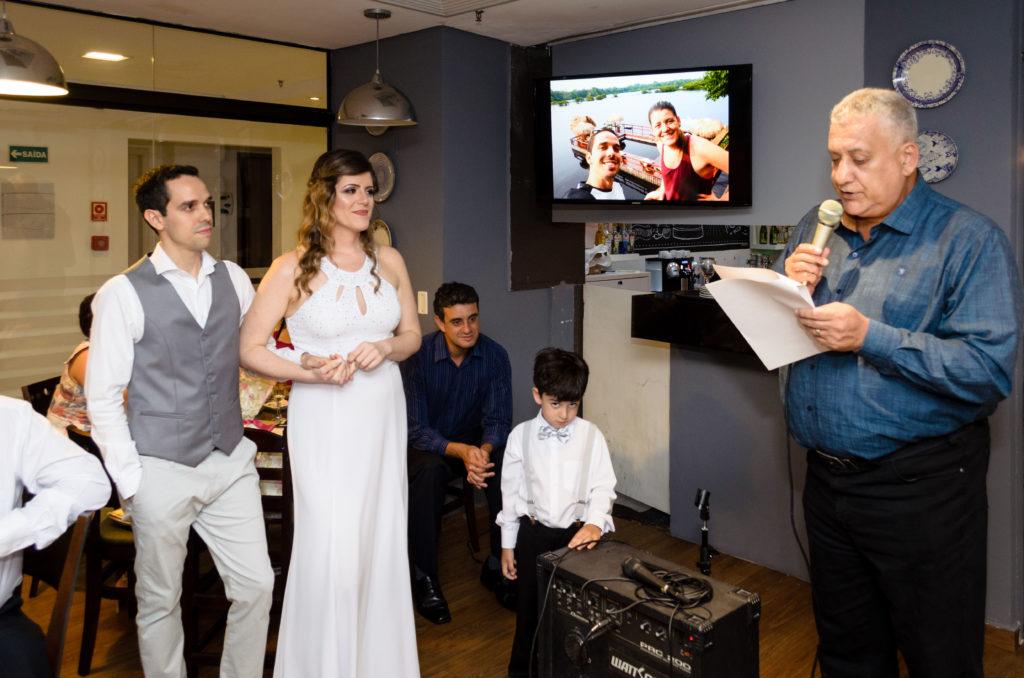 pai da noiva discursa para os noivos que o observam atentamente.