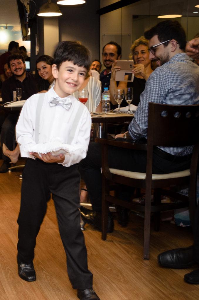 garoto em roupas sociais trás as alianças em um casamento
