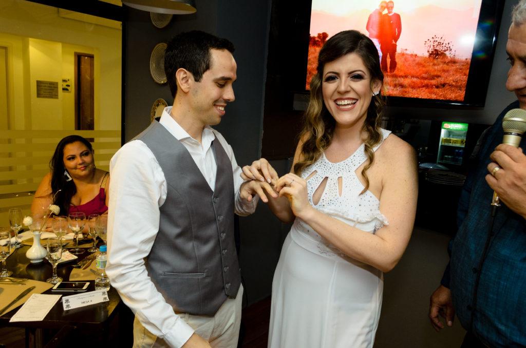 noiva muito alegre já com aliança coloca a aliança em seu noivo