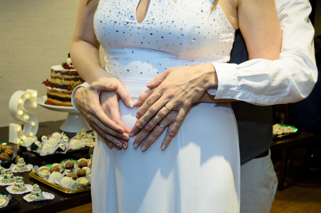 noivo atrás da noiva juntos fazerm um coração com as mãos sobre a barriga da noiva com as alianças a mostra