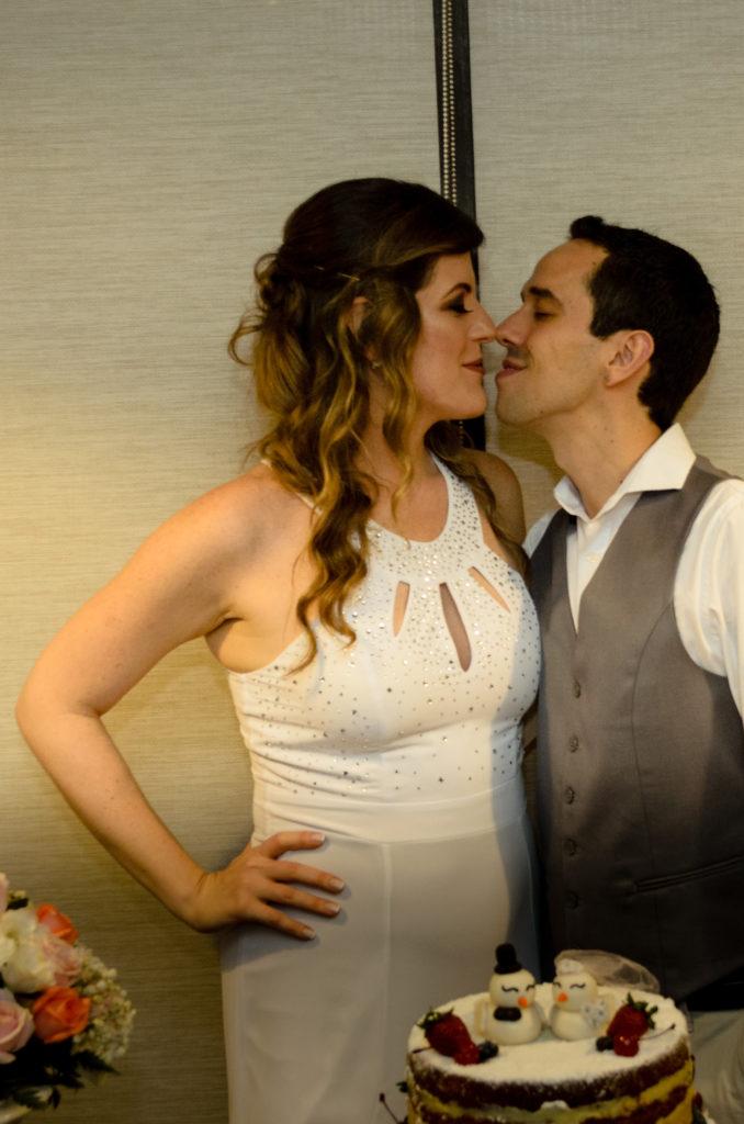 casal de noivos quase se beijando encostam os narizes