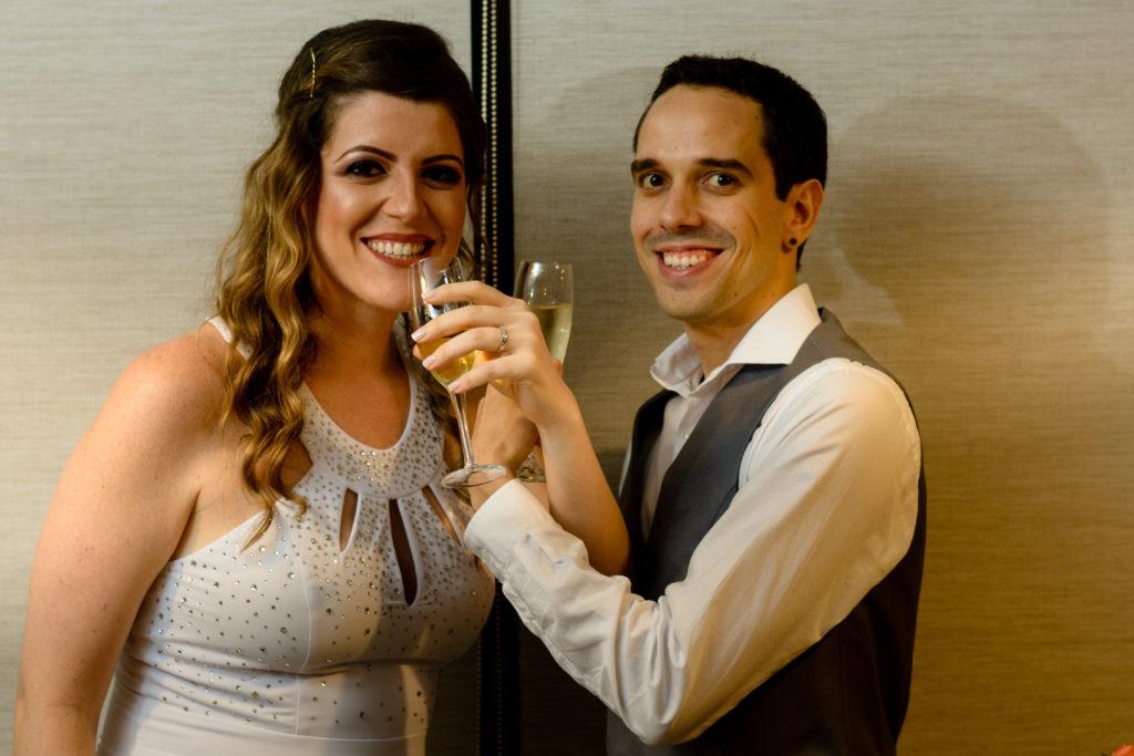 casal de noivos levam as taças de champagne ao lábios com os braços entrelaçados