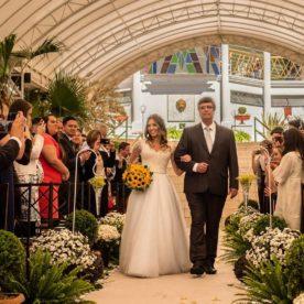 fotografia de casamento de uma noiva com seu pai entrando no corredor durante a cerimonia. convidados observam, fotografam e filmam com sues celulares.